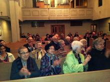 Concert goers applaud the moving performance.